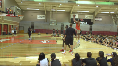 Image of Brynn Forbes Shooting Hoops at UIW While children watch