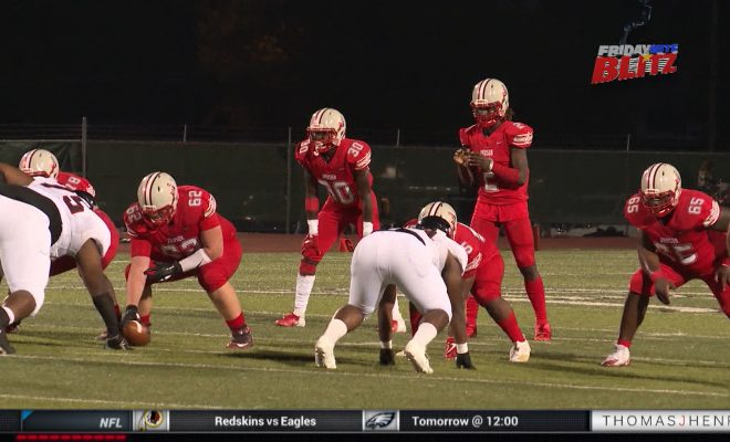 Image of two high school football teams ready to break during game