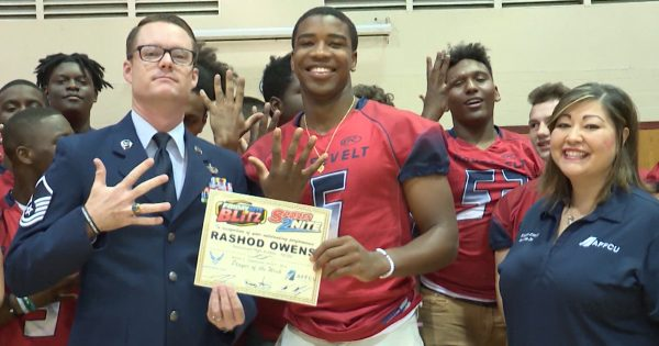 Image of Rashod Owens getting Player of the week award from an Air Force personnel