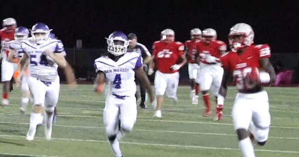 Image of football player running on field with other players behind him