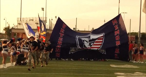 Image of Veterans Memorial football team about to ruin through their banner on field