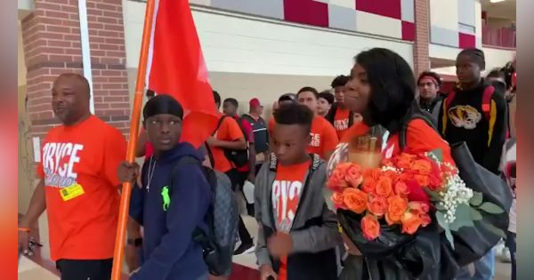 "Image of Bryce Wisdom walking in from of school parade holding ""Bryce Strong"" flag"