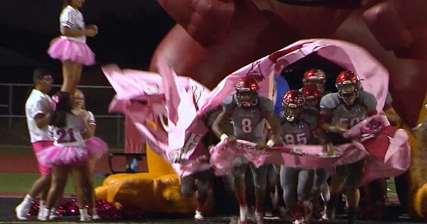 Image of high school football team running out of a big poster onto the field