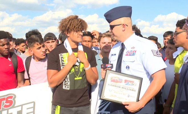 Image of Harlan High School football player Kannon Williams receiving player of the week award from SSGT Raymer Muniz