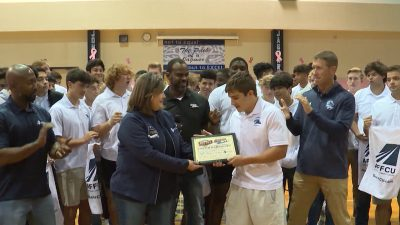Image of Justin Rodriguez receiving player of the week award from AFFCU rep Michele Harrington and Marcus Floyd around a group