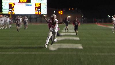 Image of a high school football player running to make a touchdown