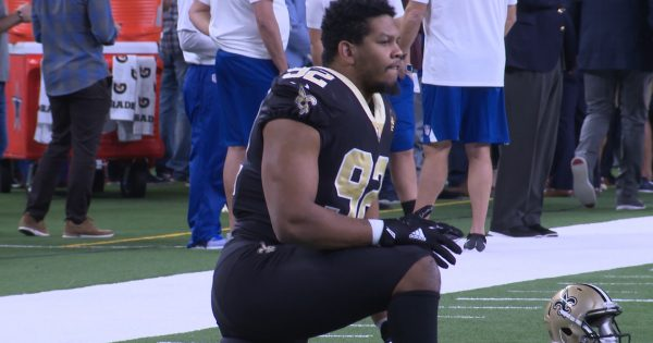 Image of Marcus Davenport stretching and kneeling on the sideline on football field