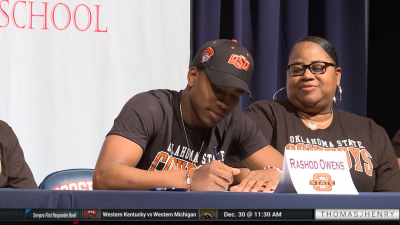 Image of high School football player signing commitment for college football