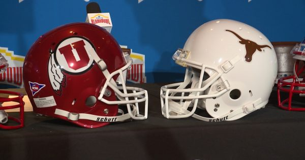 Image of Utah Utes Helmet facing Texas Longhorns helmet on table after team announcement