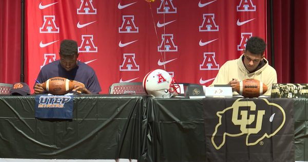 Image of Devin Grant on a table signing commitment for college football