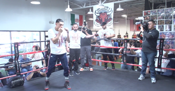 Image of Boxer in the practice ring with others around recording on camera