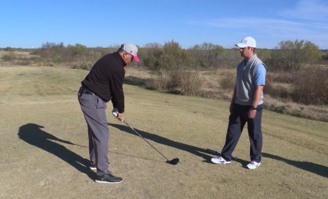 Image of Andy Everett on the green with Joe McNeil about to swing at golf ball on the ground